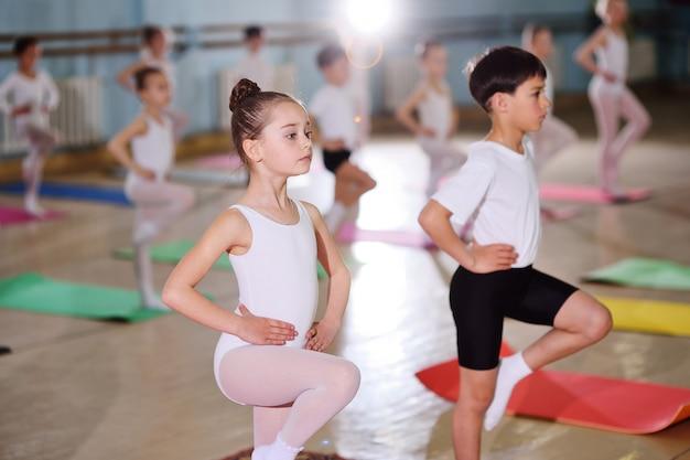 Un gruppo di bambini in una scuola di balletto o in una sezione di ginnastica sul carimatico Foto Premium