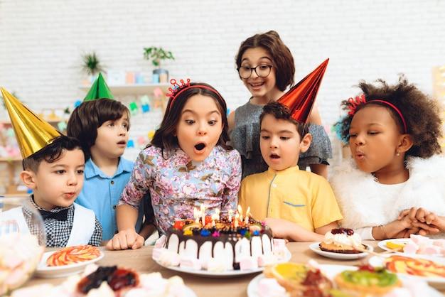 Un gruppo di bambini sta per spegnere le candeline sulla torta. Foto Premium