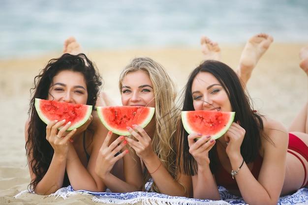 Un gruppo di belle ragazze sull'abbronzatura della spiaggia Foto Premium