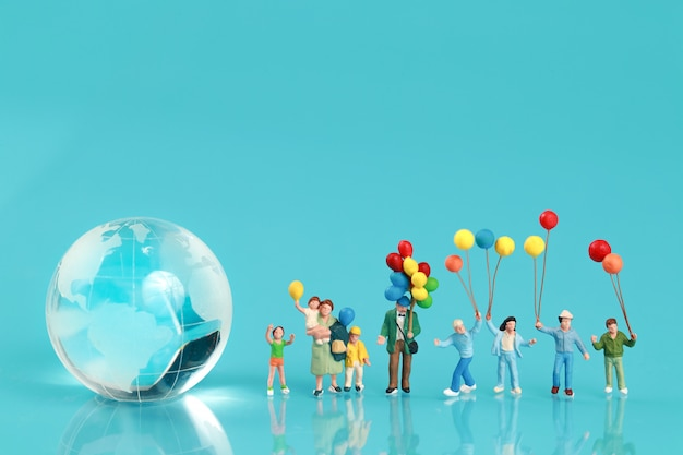 Un gruppo di famiglia felice si diverte e tiene in mano un palloncino con la terra Foto Premium