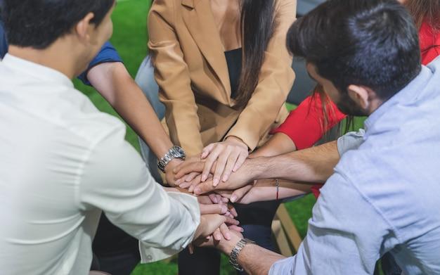 Un gruppo di giovani diversi ha problemi di vita che si tengono per mano durante la sessione di terapia Foto Premium