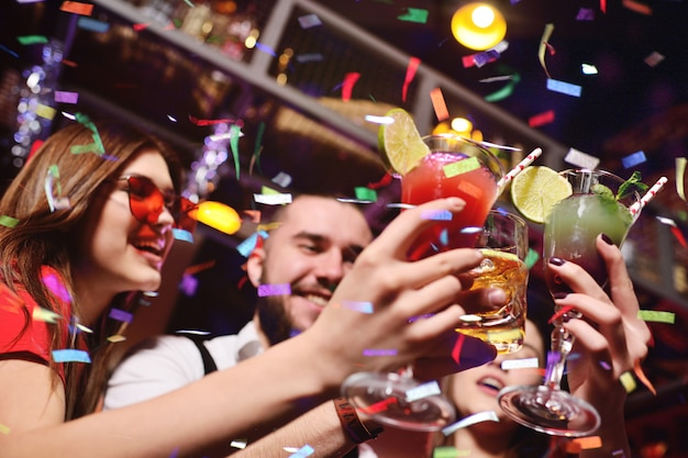 Un gruppo di giovani festeggia un compleanno o un natale in una discoteca e saluta i loro coriandoli Foto Premium