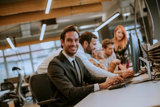Un gruppo di giovani imprenditori sta lavorando insieme al desktop computer Foto Premium