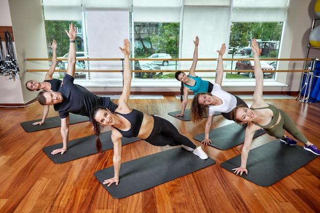 Un gruppo di giovani sportivi in abbigliamento sportivo, in una sala fitness, facendo flessioni o assi in palestra. concetto di fitness di gruppo, allenamenti di gruppo, motivazione Foto Premium