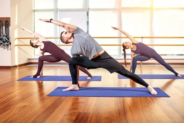 Un gruppo di giovani sportivi in abbigliamento sportivo, in una sala fitness, facendo flessioni o assi in palestra. Foto Premium