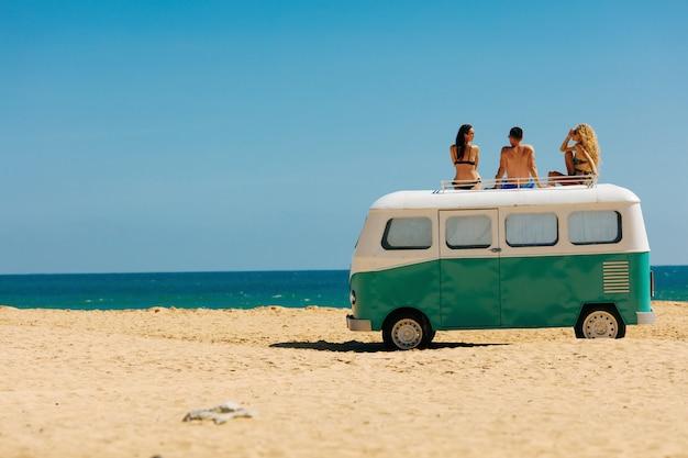 Un gruppo di tre amici che godono dei giorni di sole sull'automobile del hippie Foto Premium