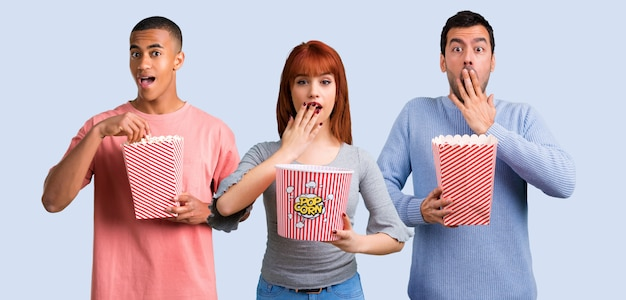 Un gruppo di tre amici che mangiano i popcorn Foto Premium