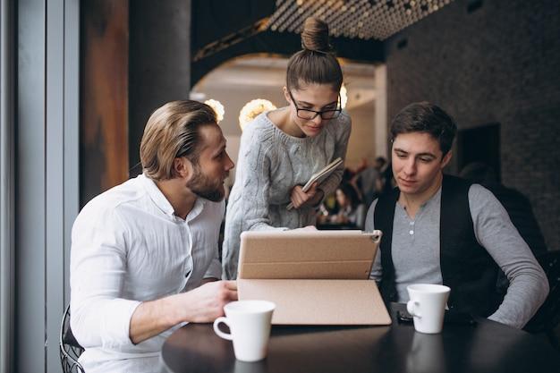 Un gruppo di tre genti che lavorano ad un progetto su un ridurre in pani in un caffè Foto Premium