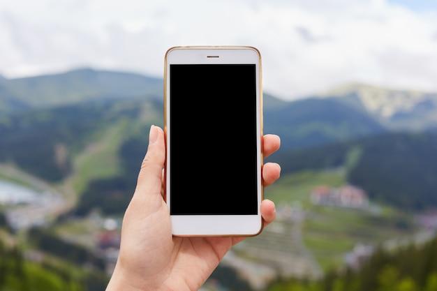 Un'immagine all'aperto di una mano che tiene e che mostra smartphone bianco con lo schermo da tavolino nero in bianco Foto Gratuite