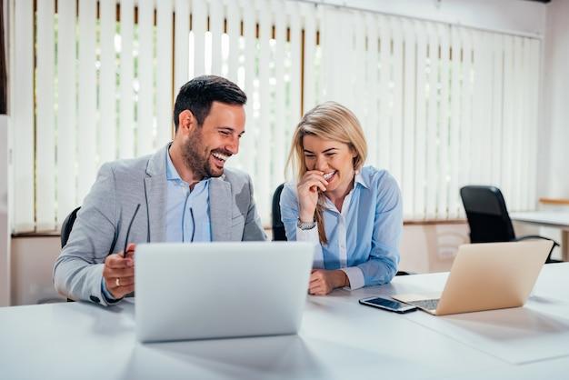 Un'immagine del primo piano di due genti di affari che ridono nell'ufficio coworking. Foto Premium