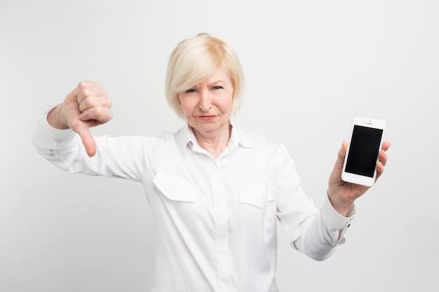 Un'immagine della signora matura con il nuovo smartphone. lo ha testato e ha ammesso che questo telefono è cattivo. ecco perché mostra un grande pollice verso il basso. Foto Premium