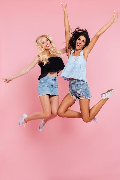 Un'immagine integrale di due amici felici che saltano nello studio Foto Gratuite