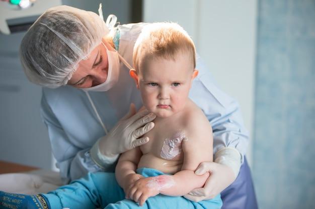 Un'infermiera di un ragazzino tratta un'ustione. un bambino in ospedale è ferito. il medico tratta il bambino. piccolo paziente ricoverato. Foto Premium