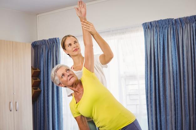 Un istruttore di fitness che aiuta senior facendo esercizi Foto Premium