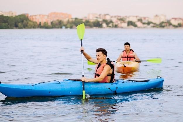 Un kayak maschio di due rematori sul lago Foto Gratuite