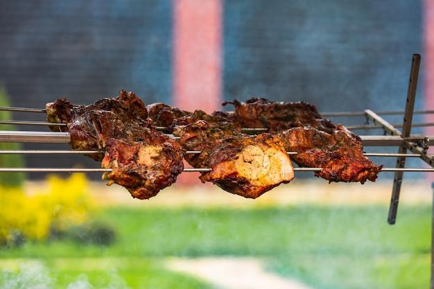 Un kebab shish rovesciato su uno spiedino pende su un fuoco. questo cibo delizioso sembra appetitoso Foto Premium