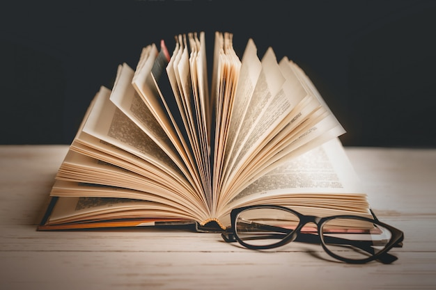 Un libro aperto con gli occhiali su un tavolo di legno sullo sfondo di una serie di libri, tonalità vintage. Foto Premium