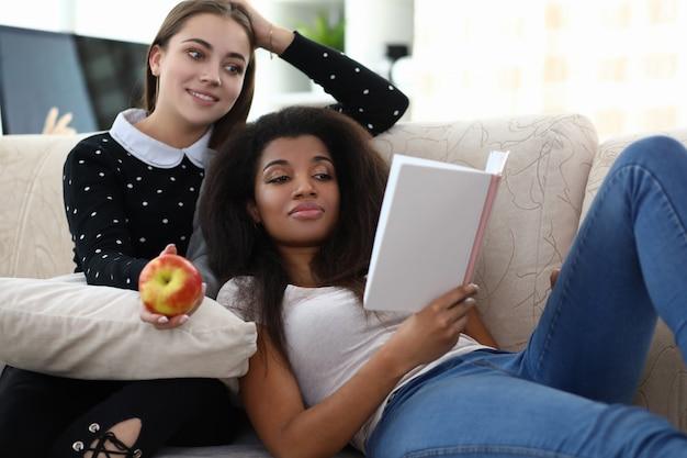 Un libro di lettura della donna di due donne si siede sull'allenatore contro Foto Premium
