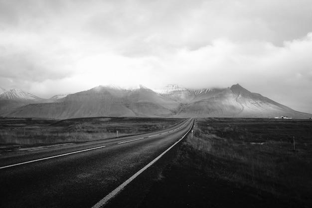 Un lungo attraverso il deserto con colline nuvolose in lontananza Foto Gratuite
