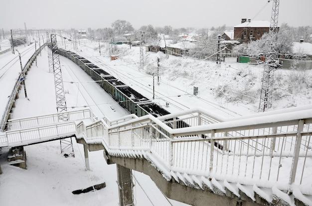Un lungo treno di vagoni merci si muove lungo il binario della ferrovia. paesaggio ferroviario in inverno dopo nevicate Foto Premium