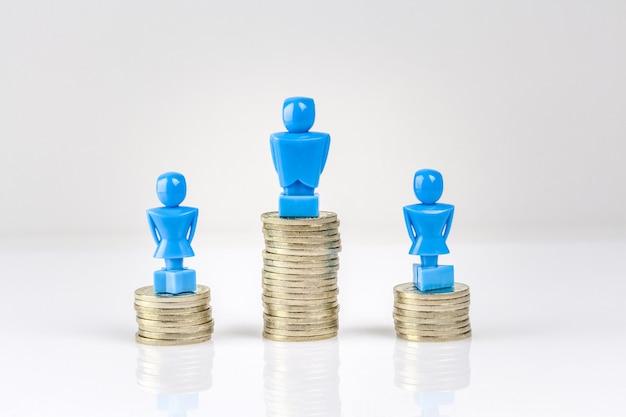 Un maschio e due figurine femminili in piedi su pile di monete. Foto Premium