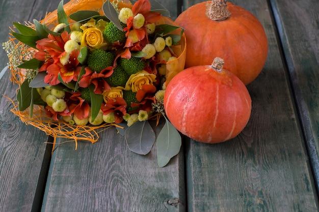 Un mazzo autunnale di fiori autunnali e rose nei toni del giallo e dell'arancio e due zucche Foto Premium
