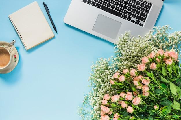 Un mazzo di fiori; tazza di caffè; blocco note a spirale; penna e laptop su sfondo blu Foto Gratuite