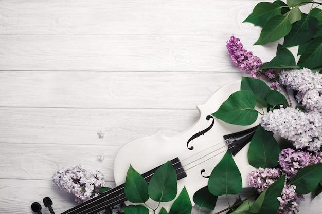 Un mazzo di lillà con violino e foglio di musica su un tavolo di legno bianco. top wiev con spazio per il testo. Foto Premium