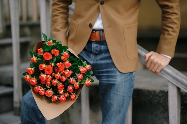 Un mazzo di rose in mani maschili. Foto Gratuite
