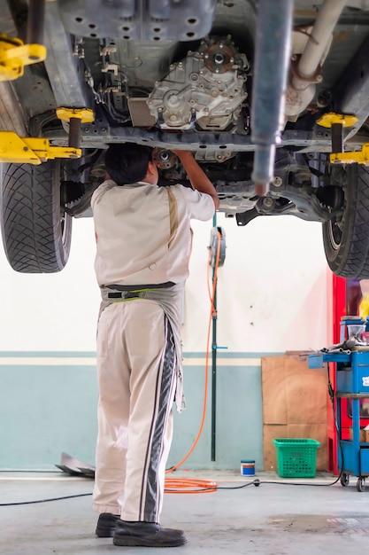 Un meccanico in piedi sotto la macchina che si trova sulla piattaforma di sollevamento, riparazione auto Foto Premium