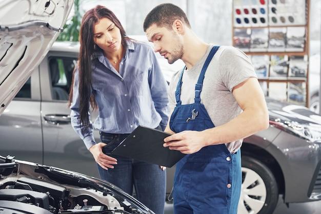 Un meccanico uomo e donna cliente discutendo riparazioni fatte al suo veicolo Foto Gratuite