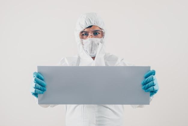 Un medico che tiene cartone bianco in guanti medici e tuta protettiva in sfondo chiaro. spazio per il testo coronavirus Foto Gratuite