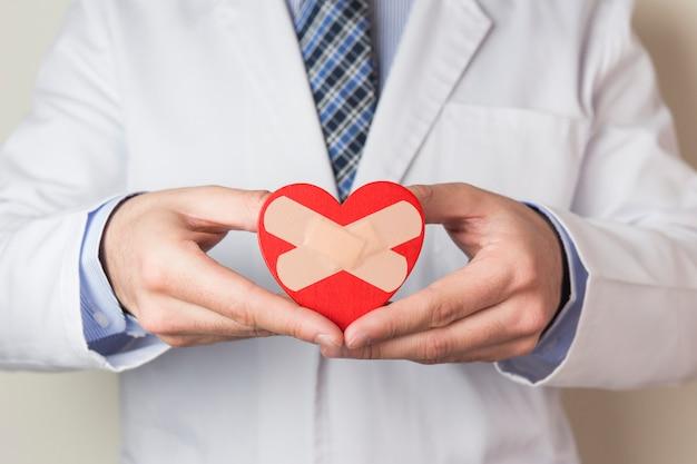 Un medico maschio che mostra cuore rosso con benda incrociata in mano Foto Gratuite
