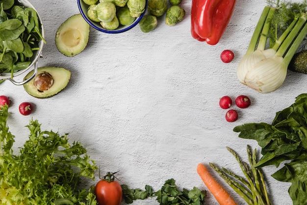 Un mix di verdure di stagione disposte su uno sfondo bianco Foto Premium