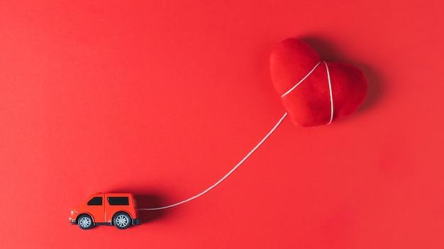 Un modello di auto rossa che rimorchia un cuscino cuore rosso su uno sfondo rosso, concetto, tema di san valentino Foto Premium