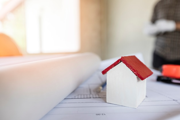 Un modello di casa di architetti con piano e progetti sulla scrivania dell'architetto Foto Premium