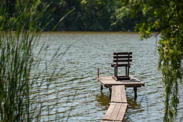 Un molo di legno su un lago con una sedia da pesca Foto Premium