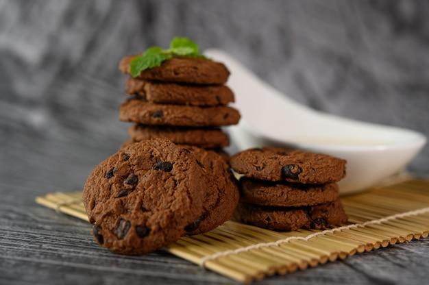 Un mucchio di biscotti e un cucchiaio di latte su un panno su un tavolo di legno Foto Gratuite
