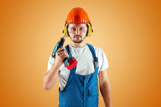 Un muratore maschio in un casco arancione tiene un cacciavite su uno sfondo arancione. Foto Premium