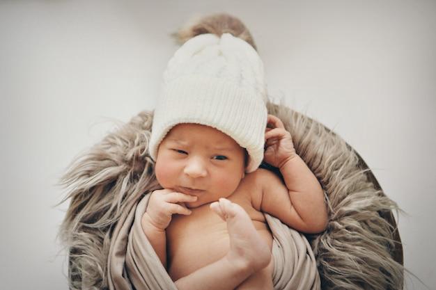 Un neonato avvolto in una coperta con un cappello caldo in testa. l'infanzia, la salute, la fecondazione in vitro. Foto Premium