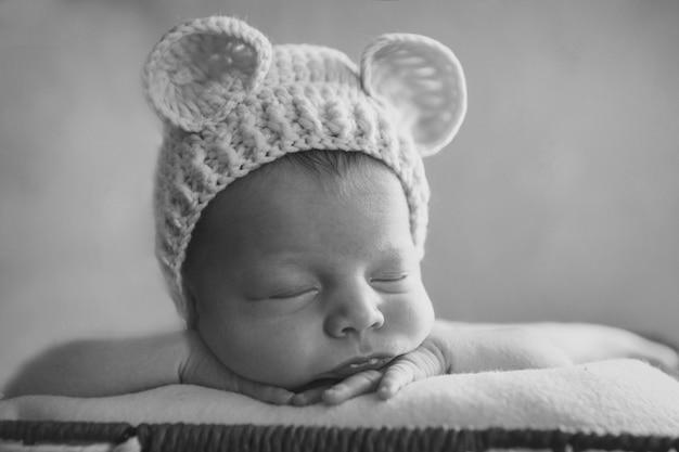 Un neonato in un cappello a maglia con orecchie. imitazione di un bambino nel grembo materno. ritratto di un neonato. il concetto di salute, genitorialità, festa dei bambini, medicina, fecondazione in vitro, moda Foto Premium