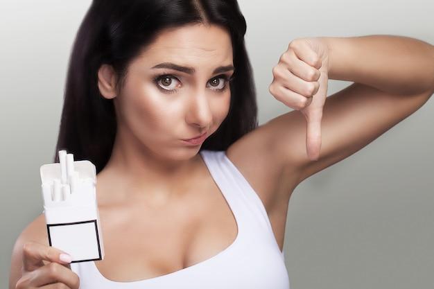 Un pacchetto di sigarette nelle mani di una donna. sguardo stupito alle sigarette. contro il fumo Foto Premium