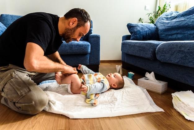 Un padre coinvolto nel prendersi cura dei suoi figli cambiando il pannolino sporco della figlia. concetto di conciliazione familiare di lavoro Foto Premium