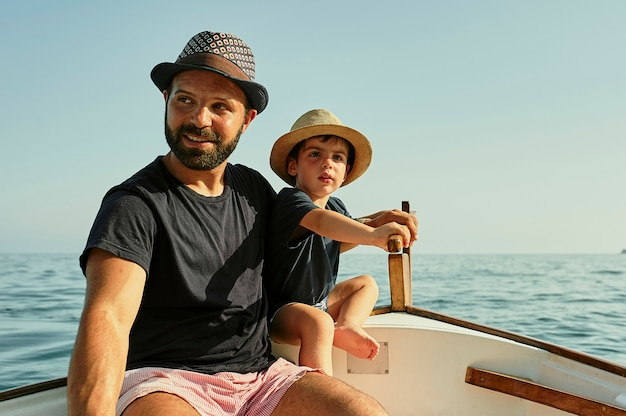 Un padre insegna a navigare a suo figlio in una barca classica Foto Premium