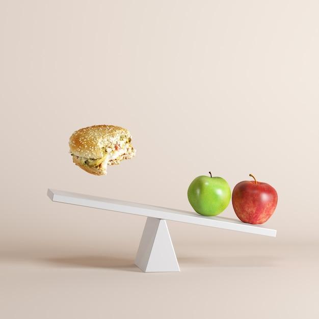 Un paio di mele oscillanti oscillanti con galleggiante sul lato opposto su sfondo pastello. Foto Premium