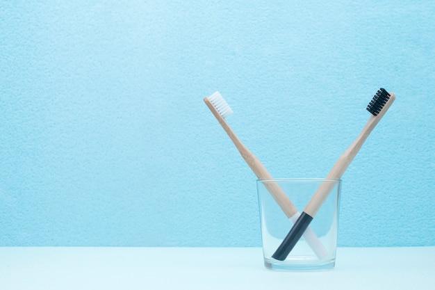 Un paio di spazzolini da denti in bambù in un vetro trasparente sul blu Foto Premium