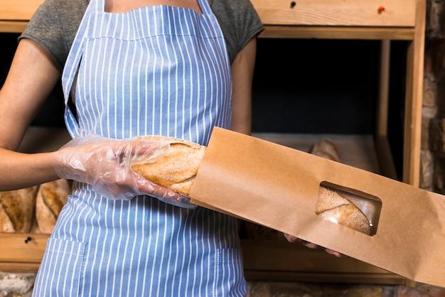 Un panettiere femmina in grembiule che impacchetta il pane baguette nel sacchetto di carta marrone Foto Gratuite