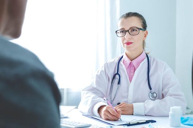 Un paziente riceve una dottoressa nell'ufficio della clinica. Foto Premium