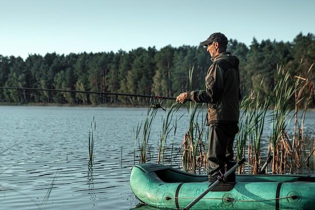 Un pescatore di sesso maschile sul lago è in piedi in acqua e pesca una canna da pesca vacanza di hobby di pesca Foto Premium