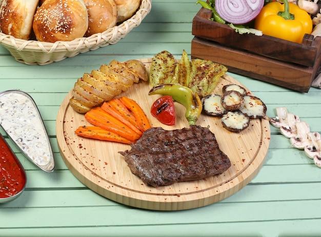 Un pezzo di bistecca con verdure grigliate sulla tavola di legno. Foto Gratuite